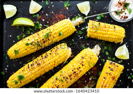 Grilled corn cobs in mexican style with lime, cilantro, chili and white sauce on black background. Top view. #1640423410