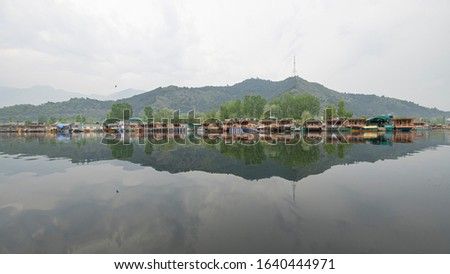 Houseboats and tourist boats on the Dal Lake on the background of mountain. Kashmir, Srinagar is famous for its floating houses and the beauty of its scenic lakes. India. #1640444971