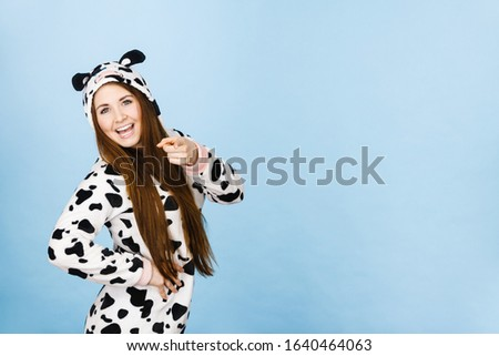 Happy teenage girl in funny nightclothes, pajamas cartoon style pointing at copy space with positive face expression, studio shot on blue. Advertisement concept
