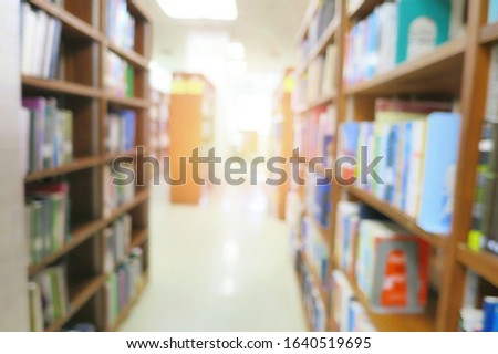 Blurred of the interior of the public library with books in wooden bookshelves. Education and book's day background concept. #1640519695