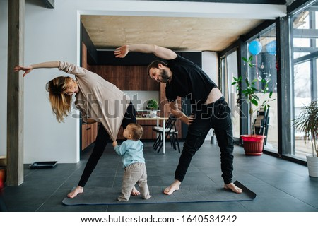 Family doing yoga. Mother and father doing side tilts as a part of their morning exercise, while their child pulling mother's shirt, seeking attention. #1640534242
