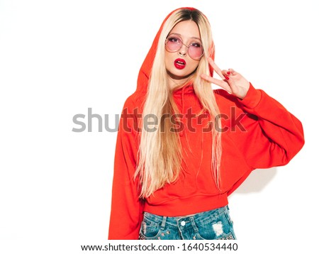 Portrait of young beautiful hipster bad girl in trendy red summer hoodie and earring in her nose.Sexy carefree smiling blond woman posing in studio.Positive model having fun.Isolated on white