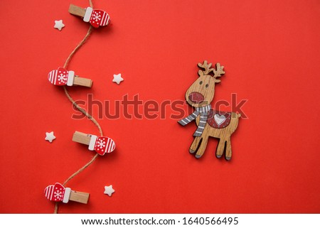 Christmas decorations decorative background. Decorative pins in the form of red gloves and a wooden deer on a red background. Top view, minimalism, flat layout. #1640566495