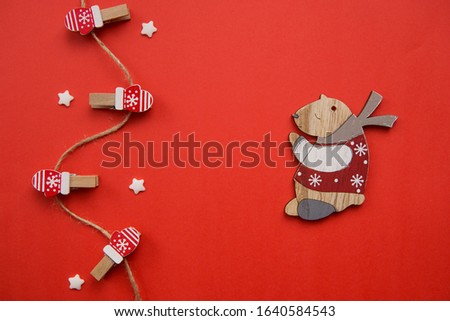 Christmas decorations decorative background. Decorative pins in the form of red gloves and a wooden bear on a red background. Top view, minimalism, flat layout. #1640584543