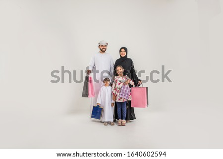 Middle eastern family with traditional emirates dresses posing in a photographic studio - Concepts about lifestyle, happiness and family relationship in the UAE
