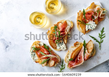 Appetizer crostini, tapas, open faced sandwiches with pear, prosciutto, arugula and blue cheese on white marble board. Delicious snack, appetizers #1640609239