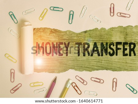 Text sign showing Money Transfer. Conceptual photo The act of transferring money from one place to another place Stationary and torn cardboard placed above a wooden classic table backdrop. #1640614771