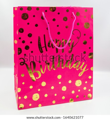 cute pink colored shopping bag with happy birthday written on it: joy and gift