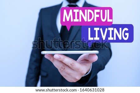 Writing note showing Mindful Living. Business photo showcasing Having a sense of purpose and setting goals in life Male human wear formal work suit hold smartphone using hand. #1640631028