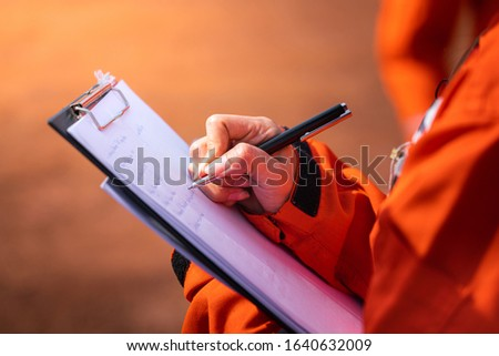 Safety officer/Supervisor is writing note on the checklist paper during perform audit and inspection in oil field operation. Close-up action and selective focus photo.