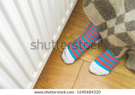 A child warms his legs under a woolen warm blanket near a home heater in cold winter time. The symbolic image of the heating season at home.  #1640684320
