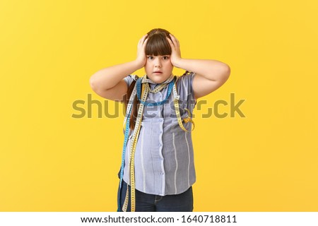 Stressed overweight girl with measuring tapes on color background #1640718811