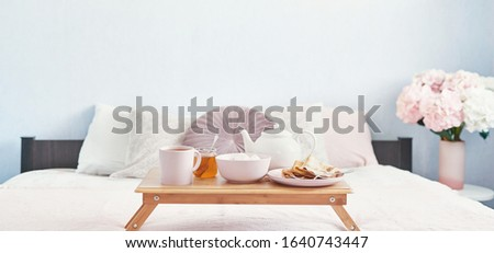 Breakfast in bed in hotel room. Accommodation. Breakfast in bed with tea cup with pancakes on tray on bed background top view. Copy Space. Romantic valentine's day breakfast. Cozy breakfast Maslenitsa #1640743447