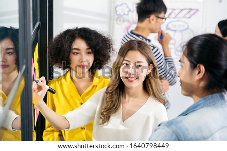 Group of Asian business people meeting at modern office .Young creative team use post it notes to share idea sticky note on glass wall. and working design planning and Brainstorming concept.  #1640798449