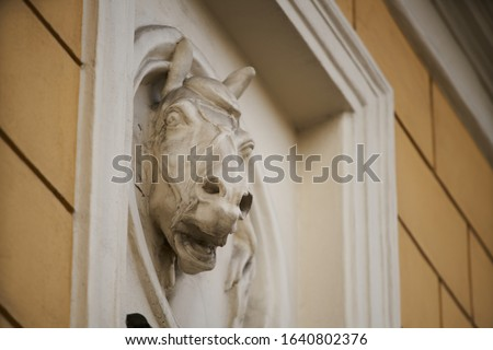 Old horse head sculpture made of stone at entrance of a house Royalty-Free Stock Photo #1640802376