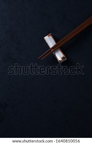 Wooden chopsticks and chopstick rest on dark stone background. Top view. Copy space.  #1640810056