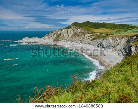 The north Devon coast at Rockham Beach showing steeply inclined slate strata of the Morte Slates Formation - sedimentary bedrock formed in the Devonian Period. Taken from the South West coast path. Royalty-Free Stock Photo #1640880580