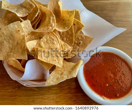 A basket with corn tortilla chips and red salsa for appetiser.