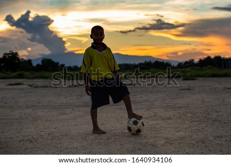 Action sport outdoors of poverty kids having fun playing soccer football for exercise in community rural area under the twilight sunset sky. Picture with copy space.