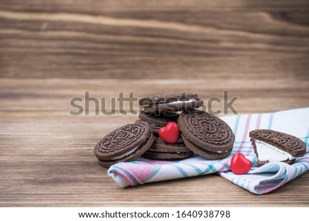 chocolate chip cookie sandwich on a colored napkin on a wooden background. wooden and red hearts. Happy Valentine's day. beautiful picture with biscuits. texture.