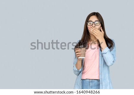 Young tired sleepy indian girl student feel exhausted holding coffee cup yawning isolated on gray studio background, funny lazy bored teen feeling deprived drowsy during exam preparation concept