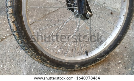 Bicycle Wheel Steel spokes and central wheel mount to the bike frame close-up. Nut on the bolt. Metal parts are qualitatively assembled into a product. Clay and dirt adhered to the rubber tire #1640978464