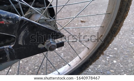 Bicycle Wheel Steel spokes and central wheel mount to the bike frame close-up. Nut on the bolt. Metal parts are qualitatively assembled into a product. Clay and dirt adhered to the rubber tire #1640978467