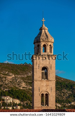 Medieval catholic church tower with bell cote, hills on background #1641029809