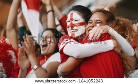 English female soccer fans with England flag painted on their faces hugging each other after their team's victory. English female spectators in football stadium celebrating their team's victory. Royalty-Free Stock Photo #1641052243