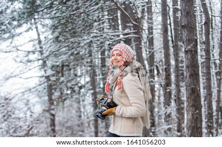 winter travel vacation. stylish hipster traveler. woman holding photo camera. taking picture in winter forest. Photographer photographing on snowy winter day. happy woman warm clothes fashion.