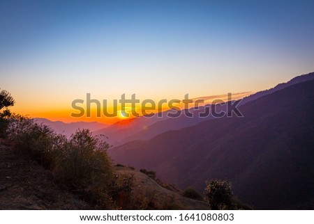 Mountains layered views from the top of Nag Tibba base camp located in Dehradun Uttarakhand India. Sunset view of the natural beauty in Nag Tibba trek located in Dehradun Uttarakhand India. - Image #1641080803