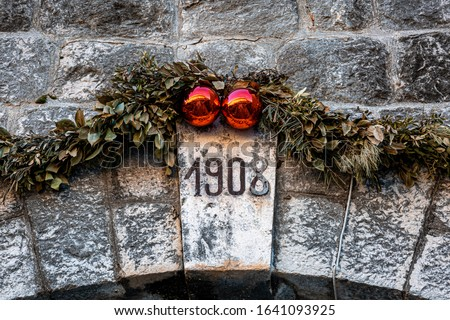 """Ancient arch closeup with """"1908"""" sign inside ancient walls in the old town of Dubrovnik with Christmas wreath decoration #1641093925"""