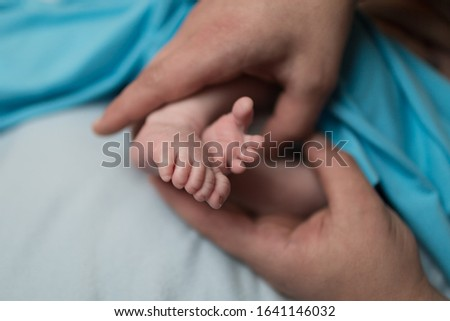 feet of a newborn child in the hands of parents.  Parental care, parental love #1641146032