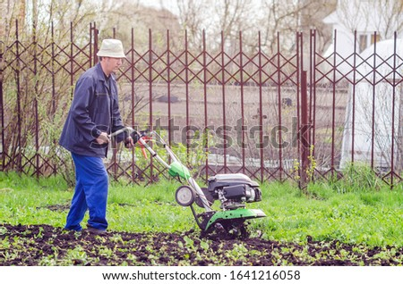A man cultivates the land with a cultivator in a spring garden. #1641216058
