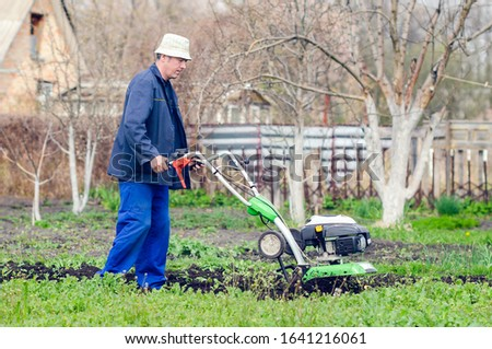 A man cultivates the land with a cultivator in a spring garden. #1641216061
