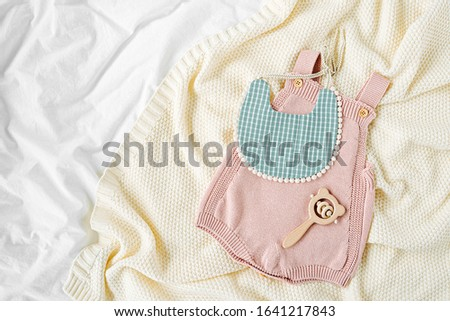 Pink bodysuit and  bib on knitted blanket. Set of  kids clothes and accessories  on bed. Fashion newborn. Flat lay, top view #1641217843