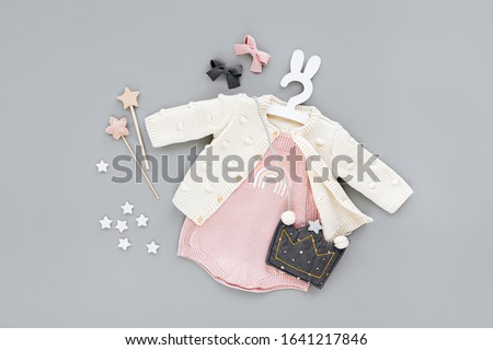 Pink bodysuit with knitted jumper, kids handbag shape of crown on cute hanger with bunny ears. Set of  baby clothes and accessories  on gray background. Fashion childs outfit. Flat lay, top view #1641217846