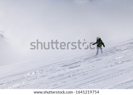 Snowboarder downhill on snowy off-piste slope with newly-fallen snow and high winter mountains in mist #1641219754