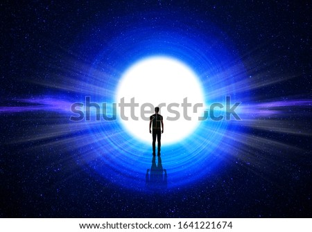 Man silhouette at the end of the tunnel with the universe and blinding light in the background Royalty-Free Stock Photo #1641221674