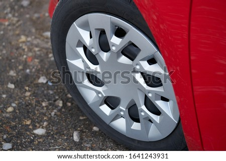 Cherry red car front detail with big light-alloy wheel. Royalty-Free Stock Photo #1641243931
