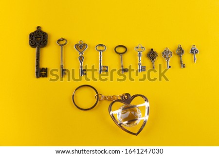 Ten different shape and size vintage keys lying in a row near heart-shaped keychain with transparent stone inside on yellow background. Top view #1641247030