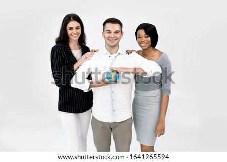 Portrait of happy young multiethnical businesspeople, African and Caucasian women, Caucasian man holding earth globe model. Diverse group of people on white background. Happy Earg day #1641265594