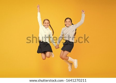 Cuties in mid air. Active children jumping high on yellow background. Happy girls enjoying active lifestyle. School friends having fun activities together. Active generation. Active and energetic. #1641270211