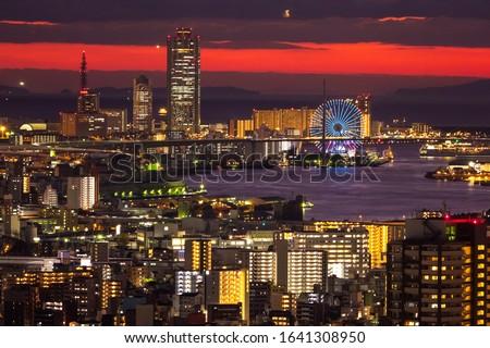 Japan. Osaka city in the evening. Osaka Bay under a black and red sky. Sunset over the Japanese city. Ferris wheel in Osaka. Ferris wheel with evening illumination. Ferris Wheel Tempozan. #1641308950