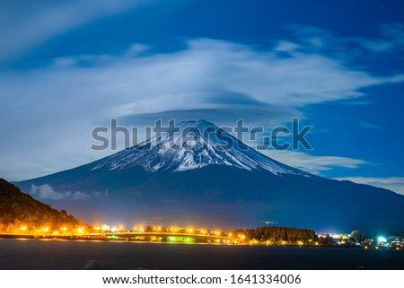 Japan. Volcano Fudziyama. Kawaguchiko lake in the evening. Mount Fuji is bombarded with snow. The lights of the evening city at the foot of the volcano. Landscape of lake Kawaguchiko. #1641334006
