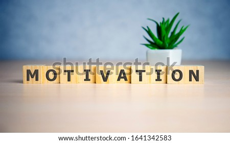 Motivation words MOTIVATION made from wooden cubes. blue background. #1641342583