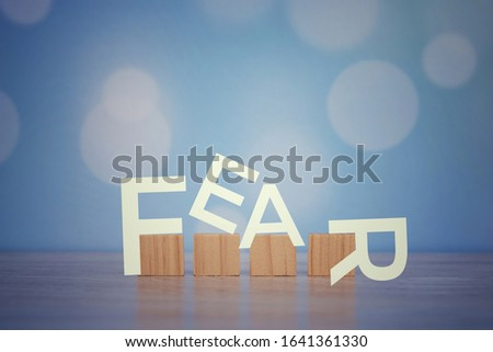 Fear. Single word. With wooden blocks on blue background. Motivational text with Vintage style design on blurry soft blue bokeh backgrounds. Face and beat the fear concept. #1641361330