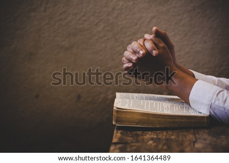 Hands folded in prayer on a Holy Bible in church concept for faith, spirituality and religion, woman praying on holy bible in the morning. woman hand with Bible praying. Royalty-Free Stock Photo #1641364489