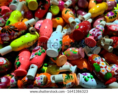 Close-up image of a pile of brightly colored whistles made of wood for sale in a gift shop. #1641386323