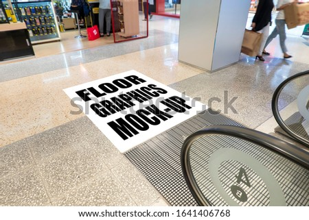 Mock up perspective blank square screen on floor with clipping path at front of escalator in shopping mall, empty space for insert graphic or text information or warning word, Blurred people walking